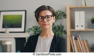 Portrait of young attractive businesswoman standing in office looking at camera