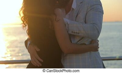 Portrait of young attractive couple dancing latin bachata near sea or ocean. Sunlight background. Summer time, romantic footage. Slow motion
