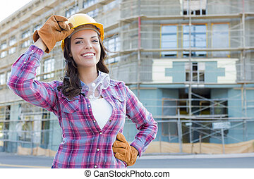 Portrait of Young Attractive Female Construction Worker Wearing Gloves, Hard Hat and Protective Goggles at Construction Site.