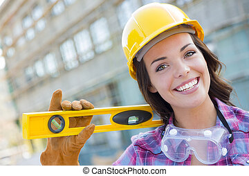 Portrait of Young Attractive Female Construction Worker with Level Wearing Gloves, Hard Hat and Protective Goggles at Construction Site.