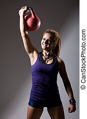 Portrait of young attractive female doing kettle bell exercise o