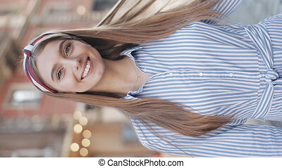 Portrait of Young Attractive Girl with Brown Hair and Fashionable Headband Wearing in Striped Dress Turning Head to Camera Swapping Hair and Smiling Standing at the City Street Vertical Video