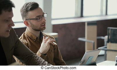 Portrait of young attractive man at business meeting with boss. People discussing new project in modern office.