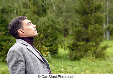 Portrait of young attractive man with a grey coat, breathing in the fresh autumn air in the Park, showing his face to the wind. The concept of freedom, ecology, life without borders