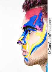 portrait of young attractive man with colored face paint on...