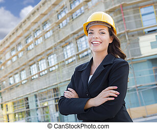 Portrait of Young Attractive Professional Female Contractor Wearing Hard Hat at Construction Site.