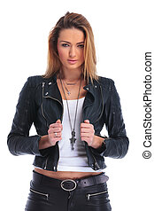 attractive woman fixing her leather jacket while posing in studio background