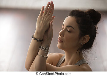 Portrait of young attractive woman meditating with closed eyes,