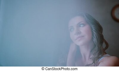 Portrait of young attractive woman standing near the window. Girl looking afar and dreaming. View through the curtain.