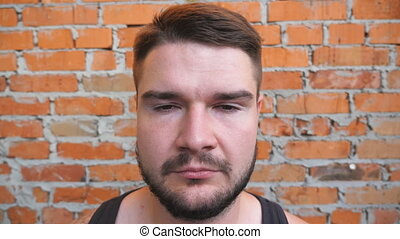 Portrait of young bearded guy looking into camera with confident and serious expression on his face outdoor. Close up of strong man with brown hair standing on blurred brick wall background