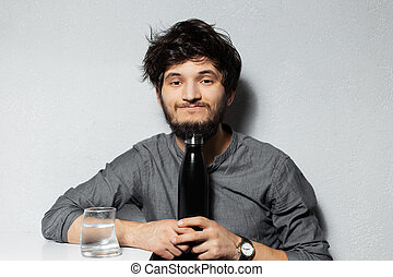 Portrait of young bearded guy with disheveled hair, holding steel thermo bottle, near glass with water, on background of grey.