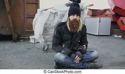 Portrait of young bearded homeless man sitting on a sidewalk...