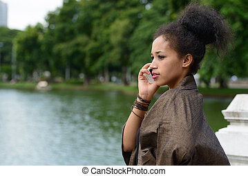 Portrait of young beautiful African woman talking on the phone at the park
