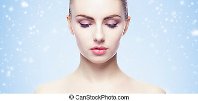 Portrait of young, beautiful and healthy woman over winter Christmas background.