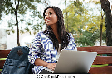 Portrait of young beautiful asian female student with laptop, sitting on wooden bench in park