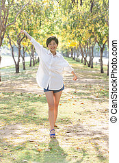 portrait of young beautiful asian woman standing in park with re