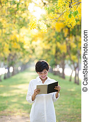 portrait of young beautiful asian woman standing in yellow flowe