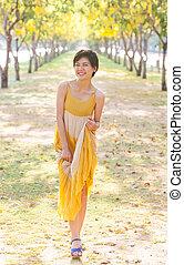 portrait of young beautiful asian woman wearing yellow dress rel