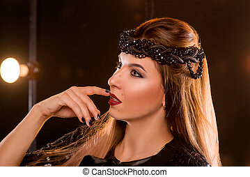 portrait of young beautiful attractive long hair woman in black wreath with hand nearly her mouth