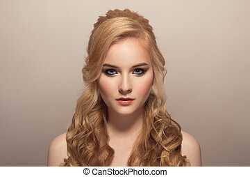 Portrait of young beautiful blond woman. Hairstyle and make-up.