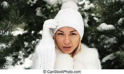 Portrait of young beautiful blonde in winter forest.