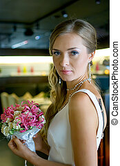 beautiful bride with flowers in cafe