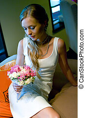 bride with flowers in cafe