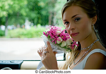 bride with flowers in car
