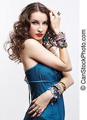 portrait of young beautiful brunette woman in blue dress and jewelery
