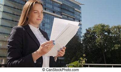 Portrait of Young Beautiful Business Woman Holding And Browsing Papers Outdoors