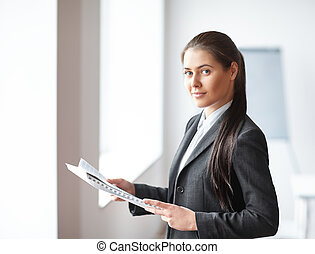 Portrait of young beautiful business woman with documents in the office