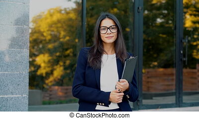 Portrait of young beautiful businesswoman looking at camera with smile outdoors, professional female manager wearing glasses and suit, holds documents folder. Student girl concept