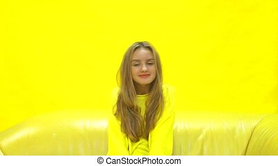 girl sitting on yellow couch, smiling at camera