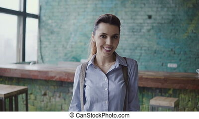 Portrait of young beautiful caucasian woman in modern coworking space. Businesswoman looking at camera, smiling,