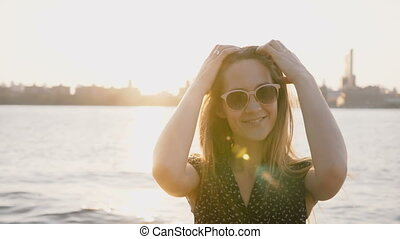 Portrait of young beautiful flirty European girl in sunglasses smiling at camera on New York city river sunset 4K.