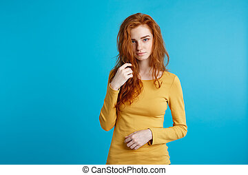 Portrait of young beautiful ginger woman confident looking at camera. Isolated on pastel blue background. Copy space.
