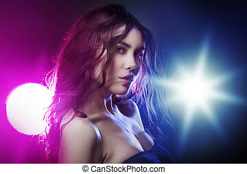 Portrait of young beautiful girl brunette, amid spotlight. The effect toning, night club, dance culture