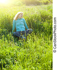 Portrait of young beautiful girl in a grassy field at sunset.