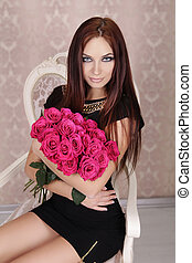 Portrait of young beautiful girl with pink roses flowers. Fashion photo
