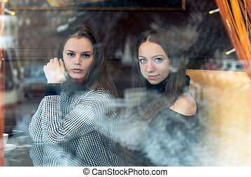 Portrait of young beautiful girlfriends in a cafe, shooting behind a glass