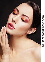 Portrait of young beautiful glamorous woman with colorful make-up touching her face