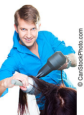 Portrait of young beautiful hairdresser man wearing blue and black drying with hair dryer on isolated white background