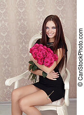 Portrait of young beautiful happy smiling girl with pink roses flowers. Fashion photo