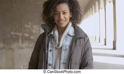 Portrait of young beautiful mixed race woman with afro haircut walking