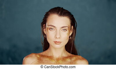 Portrait of young beautiful model girl with original golden make-up and sparkles on blue background. Concept of haute couture, art visage, femininity