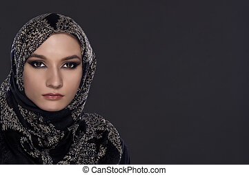 portrait of young beautiful muslim woman with head scarf