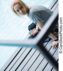 Portrait of Young Beautiful Smiling Blonde Girl Using Smartphone while Sitting on the Bridge.