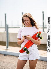 Young Beautiful Smiling Blonde Girl Using Smartphone while Sitting on the Skateboard