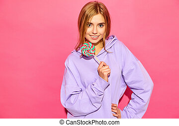 Portrait of young beautiful smiling hipster girl in trendy summer hoodie. Sexy carefree woman posing near pink wall. Positive model with lollipop