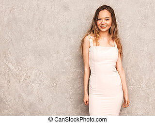Portrait of young beautiful smiling hipster girl in trendy summer light pink dress. Sexy carefree woman posing near gray wall. Positive model having fun